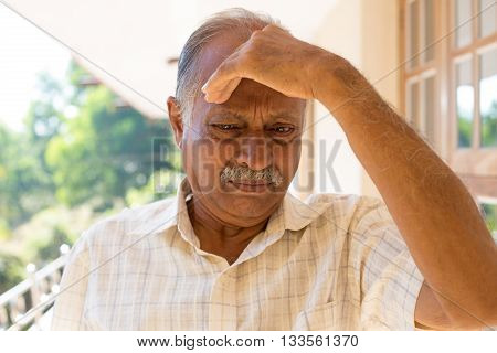 Closeup portrait morose elderly pensioner downcast gloomy resting hand on head isolated outside outdoors home background poster