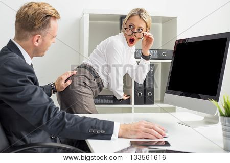 Sexual harassment at the office setup: Man touching woman's butt