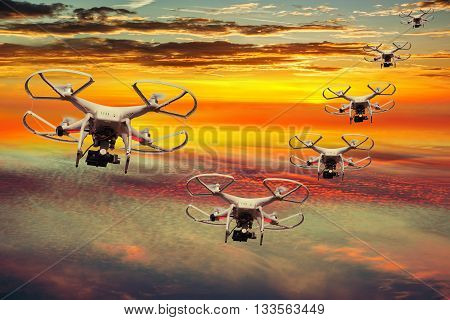 Drones squadron in the sunset with dark clouds.