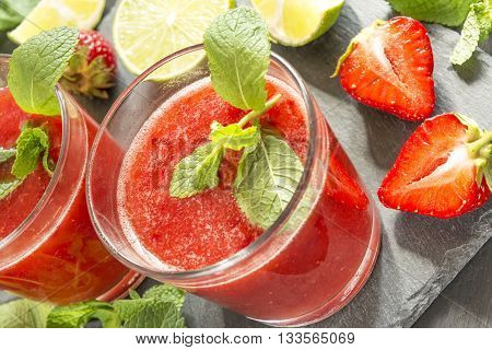 strawberry smoothie in a glass on a dark surface on a background of leaves of lemon mint and lime