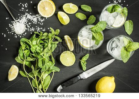 drink mojitos in the process of preparation on a dark table top view