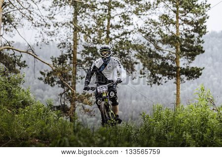 Miass Russia - May 29 2016: athlete mountainbiker in forest mountains in background during Cup