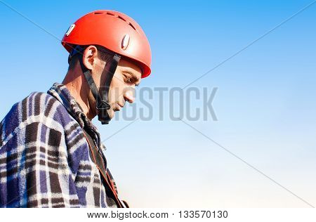 profile of the worker in a helmet. a man in a protective helmet focuses upon the work. high-altitude worker in profile on background blue sky.  copy space for your text