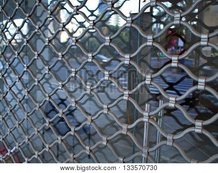 Shop window protected by iron bars security shutter against theft and vandalism