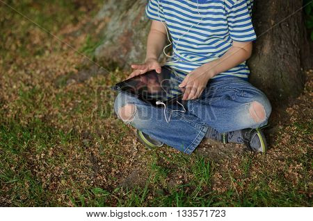 The child holds on a lap the tablet. He sits on the earth having crossed legs and having leaned against a trunk of an old tree. Jeans are torn on a lap.