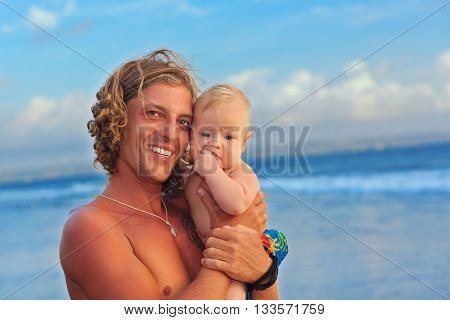 Happy family on sea beach - surfer and little son. Father with baby boy have fun on blue ocean surf and sunset sky background Healthy parent lifestyle people activity on summer vacation with children