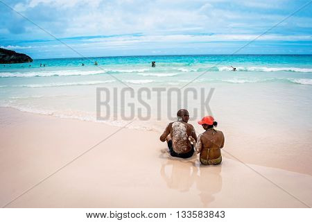 HORSESHOE BAY BERMUDA - MAY 26 - A couple relaxes on the pink sand beach in Horseshoe Bay on May 26 2016 in Bermuda.