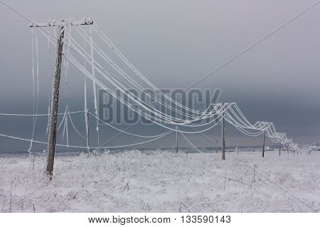 Broken phase electrical power lines with hoarfrost on the wooden electric poles on countryside in the winter pole with wires