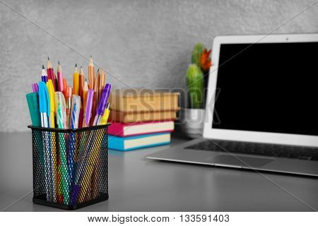 Colorful pencils and pens in metal holder on grey desk