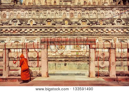 Walls of carved historical Budhist temple and lonely walking monk in yellow red dress near the gate, India. Scene near the buddhist monastery.