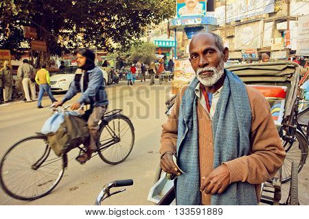 VARANASI, INDIA - JAN 1, 2016: Elderly man with white beard standing with bicycle on the busy street of Varanasi indian city on January 1, 2015. Varanasi urban agglomeration had a population of 1435113