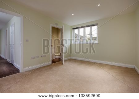 Unoccupied residential bedroom with water closet ensuite and doorway leading to hall