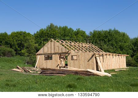 under construction wooden house on the edge of the forest bright sunny day