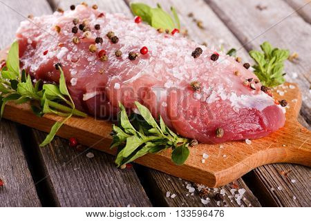 Piece Of Raw Pork Meat With Salt And Pepper On Wooden Board With Herbs