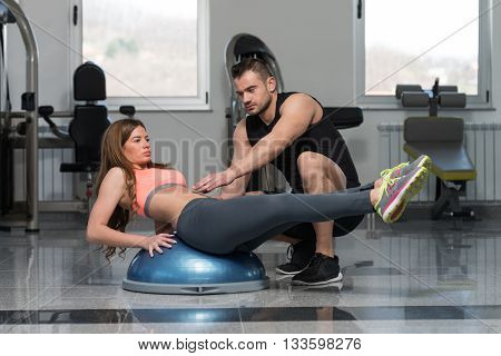 Gym Coach Helping Woman On Bosu Abs Exercise