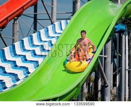 Happy family - father with son - having fun water sliding at aqua park