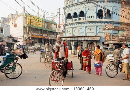 LUCKNOW, INDIA - JAN 31, 2016: Elderly cyclist driving on the busy indian street with vehicles and ancient houses on January 31, 2016. Lucknow with population of 6000455 is largest city of Uttar Pradesh