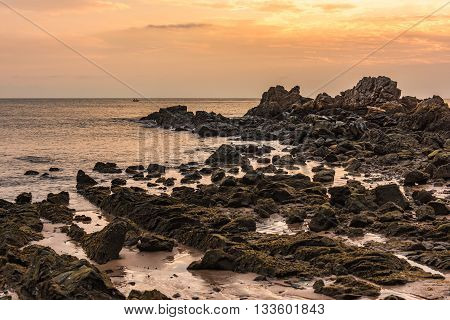 Submerged rock at coastline in the golden hour (sunset) at sea of Eastern Thailand.