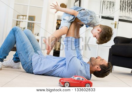 Happy father playing with son while lying on the floor at home. Young man playing with small boy. Flying child enjoying playing with dad.