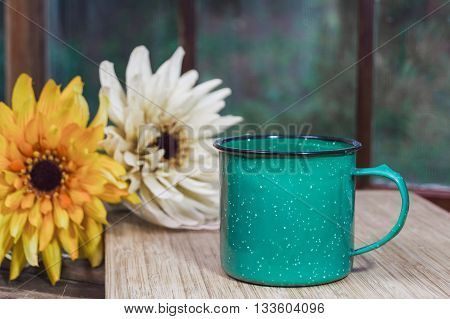 Old stoneware green coffee mug with flowers and old window in background