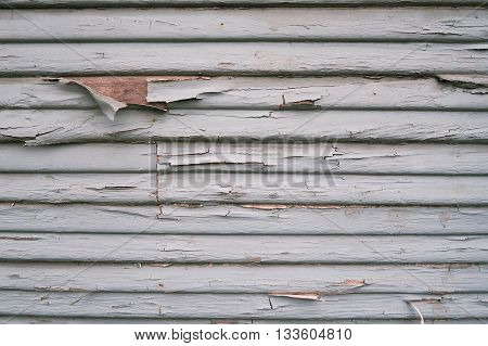 Wooden sidings of a house scratched crumbling paint