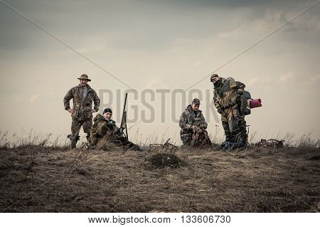 Hunters standing together against sunset sky in rural field during hunting season