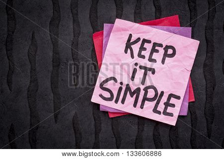 Keep it simple reminder or advice - handwriting on a sticky note against black Nepalese lokta paper