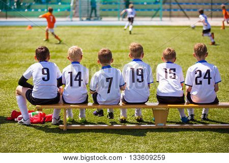 Football soccer match for children. Kids waiting on a bench at the tournament sports field.