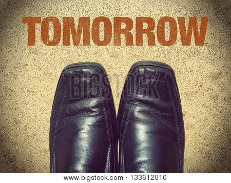 Black men shoes with word Tomorrow on street