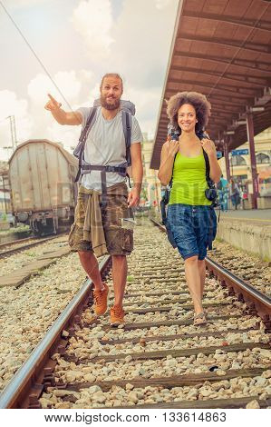 Happy and beautiful couple of tourists with backpacks walking on the tracks at the railway station near the tracks and enjoy their journey
