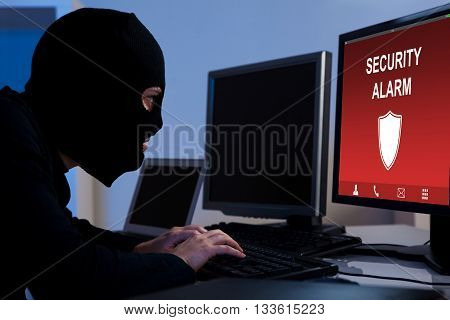 Burglar Wearing A Balaclava Breaking Security Alarm On Computer In Office