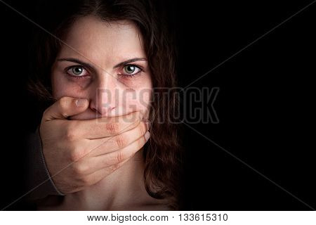 Closeup of a mans hand covering a womans mouth. Concept of domestic violence or kidnapping. Dark mood.