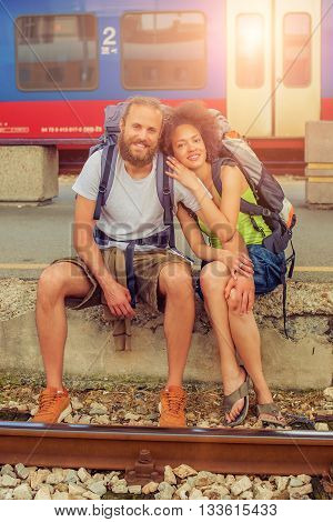 Happy young and beautiful couple of tourists with backpacks sitting at the railway station near the tracks and enjoy their journey