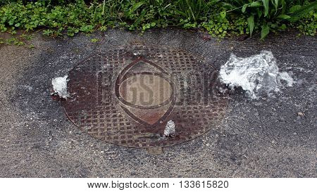 Heavy duty bolted sewer manhole cover heavily leaking water from enormous flood pressure in the local paved street.