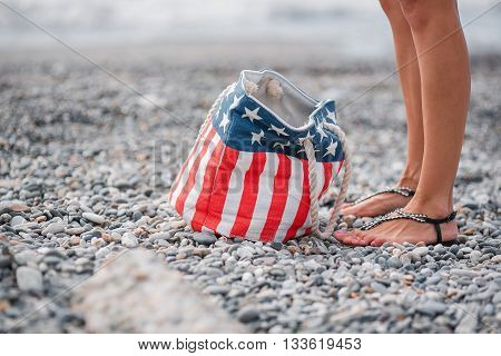 girl stand in the beach. Usa flag bag.