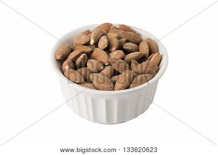 A pile of raw almonds in a white bowl or ramekin isolated on white.