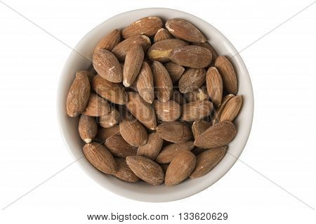 A pile of raw almonds in a white bowl or ramekin overhead view isolated on white.