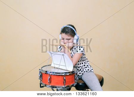 little girl boring by sitting behind the snare drum and learn a drum scores inside the studio room