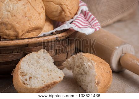 Fresh torn open dinner rolls and rolling pin in background