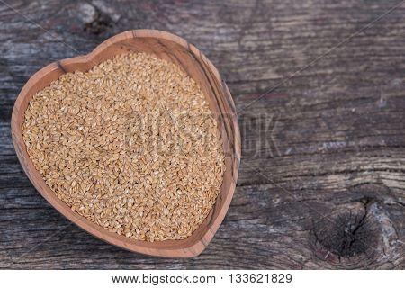 Wood heart dish with flax seeds on old barn wood