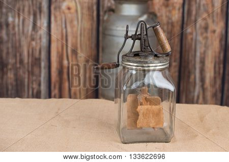 Vintage glass butter churn with copy space to the left, wooden background