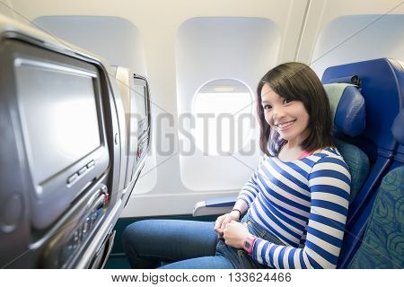 Happy young woman is sitting in the airplane asian