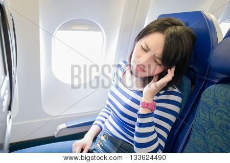 Happy young woman is sitting in the airplane feel headache asian