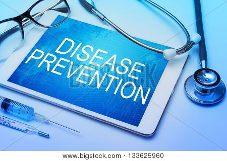 Disease prevention word on tablet screen with medical equipment on background