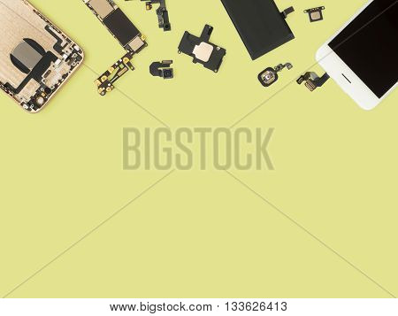 Flat Lay (Top view) of smart phone components isolate on yellow background with copy space