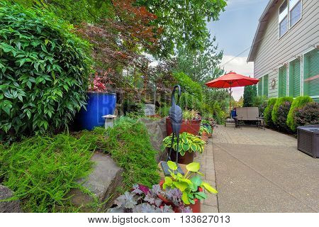 Garden Backyard patio seating red umbrella colorful container pots with plants in landscaping