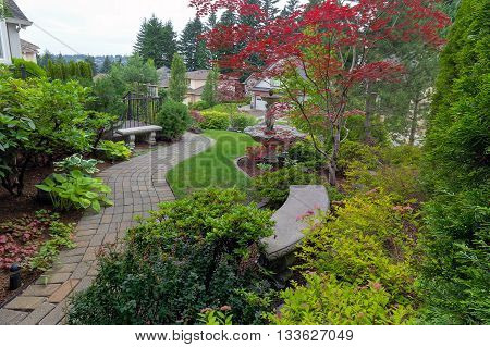 Garden brick paver path in frontyard with stone benches water fountain plants shrubs evergreen and deciduous trees landscaping
