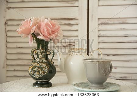 On Table A Tea Set And Flowers In Vase