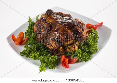 Roast chciken served on a white plate on a white background.