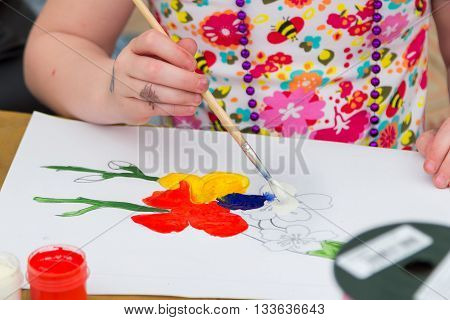 Zaporizhia/Ukraine- June 5, 2016: closeup hand of small girl, holding brush, drawing colorful flowers at painting workshop on charity family festival organized in regions with most quantity of refugees from Donetsk area, occasioned with International Chil